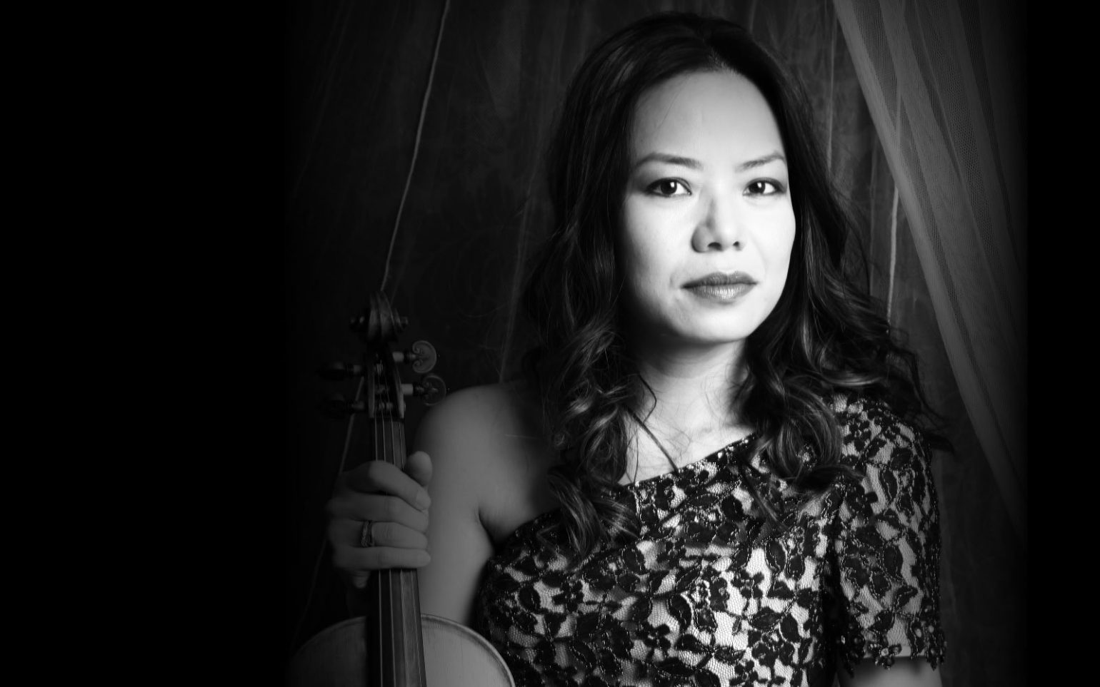 Ning Kam holding violin in front of curtain greyscale